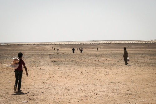 women and men make the long walk back to their shelters as  the return from the only market in the camp.